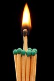 Group of green wooden matches with burning match in the centre. Isolated on black background Stock Image