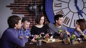 A group of grown-up friends who have not seen each other eat dinner in a restaurant, talking about the food they brought. Several men and two women with short stock video footage