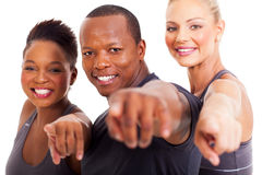 Group gym instructors. Smiling group of gym instructors pointing at the camera on white background Stock Photos