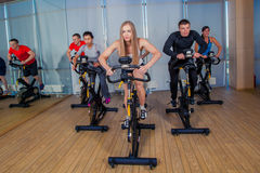 Group of gym people on machines Stock Photography
