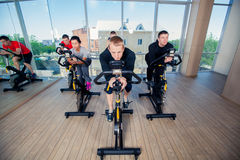 Group of gym people on machines Stock Image
