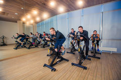 Group of gym people on machines, cycling In Class Royalty Free Stock Image