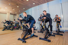 Group of gym people on machines, cycling In Class Stock Images