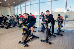 Group of gym people on machines, cycling In Class Royalty Free Stock Images
