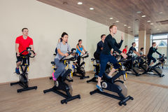 Group of gym people on machines, cycling In Class Stock Photo