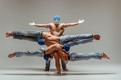 The group of gymnastic acrobatic caucasian men on balance pose. The group of gymnastic acrobatic caucasian men posing in balance posture on gray studio Royalty Free Stock Photos