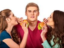 Group hamburger fast food with ham in people hands . Fast food concept. Man and women on eating party. Girls fool around and feed man. Guy on date with two Stock Photos