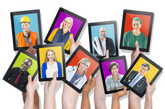 Group of Hands Holding Devices with People's Faces Royalty Free Stock Images