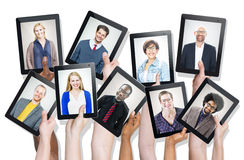 Group of Hands Holding Devices with People's Faces Stock Images