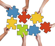 Group of Hands Holding Jigsaw Puzzle Royalty Free Stock Image