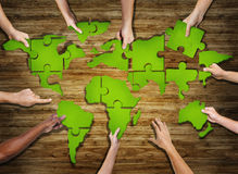 Group of Hands Holding Jigsaw Puzzle Forming World Royalty Free Stock Photography