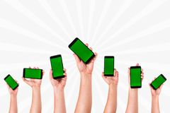 group of hands Raising up Smart phones against white background - Hands holding phones royalty free stock photos