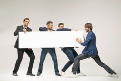 Group of handsome men pushing board. Group of handsome men pushing a board Stock Photography