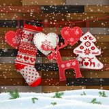 Christmas folklore decorations in front of wooden wall. Group of hanging Christmas decorations in Scandinavian style in front of wooden wall, includes hearts vector illustration