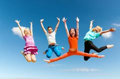 Happy active children jumping. Group of happy active children jumping outdoors royalty free stock image