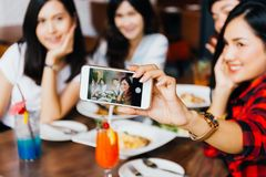 Group of Happy Asian male and female friends taking a selfie photo and having a social toast together in restaurant. royalty free stock photography