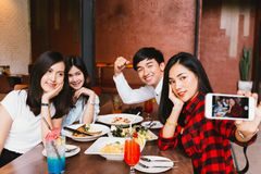 Group of Happy Asian male and female friends taking a selfie photo and having a social toast together in restaurant. royalty free stock image