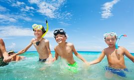 Group of happy boys in scuba mask run into the sea. Group of happy boys with scuba masks run into the sea holding hands and smiling on summer beach vacation Stock Image