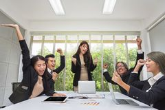 Group of happy business people cheering in office. Celebrate success. Business team celebrate a good job in the office. Asian royalty free stock photo