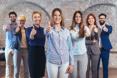 Group of happy business people and company staff in modern office. Representig company, showing thumbs up Royalty Free Stock Images