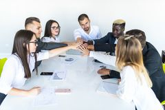Together we are stronge. Group of happy business people holding hands together while sitting around the desk royalty free stock photography