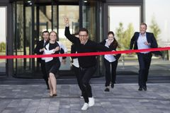 Business people crossing the finish line. Group of happy business people running from office building crossing red ribbon finish line Stock Photography