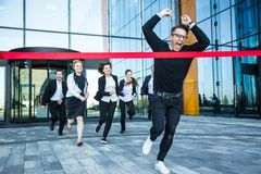 Business people crossing the finish line. Group of happy business people running from office building crossing red ribbon finish line Stock Image