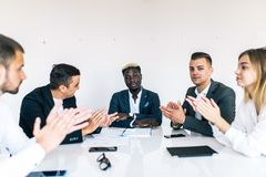 Great presentation. Group of happy business people in smart casual wear sitting together at the table and applauding to leader royalty free stock image