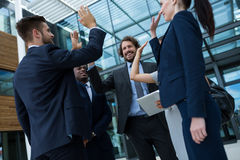 Group of happy businesspeople giving high five to each other Stock Images