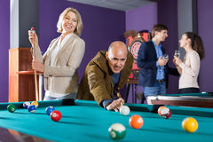 Group of happy charming  friends playing billiards Stock Image