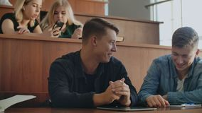 Group of happy cheerful positive smiling students with teacher in break between lessons indoors. Cheerful students are using smartphones and chatting during stock footage