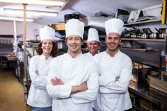 Group of happy chefs smiling at the camera. In a kitchen wearing uniforms Stock Photo