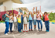 Group of happy children with arms up hold placard Stock Photos