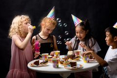Group of happy children blowing soap bubbles during birthday royalty free stock photos
