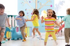 Group of happy children of boys and girls run in day care. Kids play in kindergarten. Group of happy children of boys and girls run in day care. Kids playing in royalty free stock photos