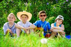 Group of happy children. Group of cheerful children resting in the park with songs and guitar. Outdoor activity. Summer holidays Royalty Free Stock Photos