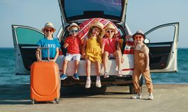 Group happy children girls and boys friends    on the car ride to summer trip royalty free stock images