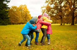 Group of happy children hugging in autumn park royalty free stock images