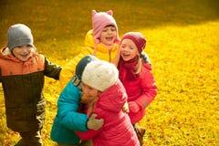 Group of happy children hugging in autumn park Stock Photo