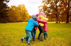 Group of happy children hugging in autumn park Royalty Free Stock Photos