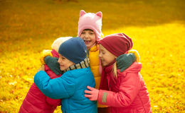 Group of happy children hugging in autumn park Royalty Free Stock Photo