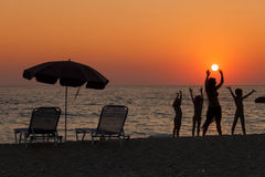 Group of happy children parting on the beach at sunset Royalty Free Stock Image