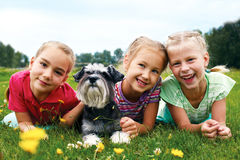 Group of happy children playing on green grass in spring park royalty free stock photo