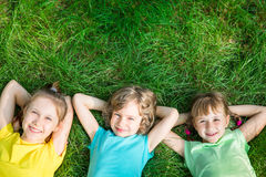 Group of happy children playing outdoors. Kids having fun in spring park. Friends lying on green grass. Top view portrait Stock Photos
