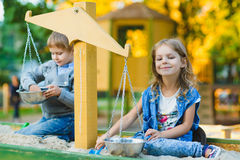 Group of happy children playing in sandbox at playground Stock Images