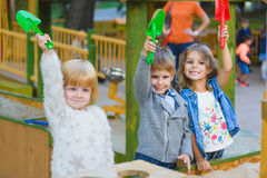 Group of happy children playing in sandbox at playground Stock Photo