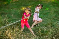 Group of happy children playing tug of war outside on grass. Kids pulling rope at park stock photo