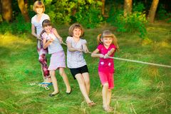 Group of happy children playing tug of war outside on grass. Kids pulling rope at park. stock photo