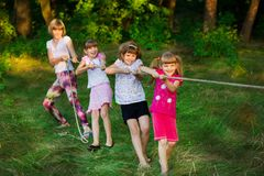 Group of happy children playing tug of war outside on grass. Kids pulling rope at park. royalty free stock photos