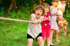 Group of happy children playing tug of war outside on grass. Kids pulling rope at park. Summer camp stock images